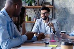 Concentración completa en el trabajo Grupo de hombres de negocios jovenes que trabajan y que comunican mientras que se sienta en  fotos de archivo
