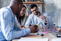 Concentración completa en el trabajo Grupo de hombres de negocios jovenes que trabajan y que comunican mientras que se sienta en  fotos de archivo libres de regalías