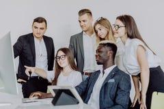 Concentración completa en el trabajo Grupo de hombres de negocios jovenes que trabajan y que comunican mientras que se sienta en  foto de archivo libre de regalías