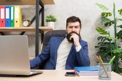 Concentración y foco El jefe barbudo del hombre sienta la oficina con el ordenador portátil Encargado que soluciona problemas de  foto de archivo