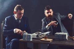 Concentraci?n completa en el trabajo Hombres de negocios que cuentan el dinero del efectivo Socios comerciales que escriben infor fotografía de archivo