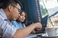 Concentrado asiático del equipo del negocio en el ordenador portátil foto de archivo libre de regalías
