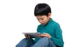Concentrado asiático del niño en la tableta de la lectura Fotografía de archivo libre de regalías