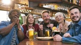 Concentrado cinco amigos jovenes que miran el partido de fútbol mientras que bebe la cerveza y el cóctel en la barra, pub almacen de metraje de vídeo