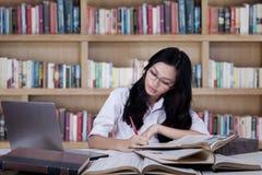 Concentrado del estudiante que estudia en biblioteca Imagen de archivo libre de regalías