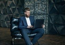 Concentraiting op project Nadenkende jonge moderne mens die computer met behulp van terwijl het zitten op zijn werkende plaats royalty-vrije stock afbeelding