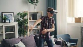 Concentran al hombre adulto en ropa informal en juego en los vidrios de la realidad virtual que colocan en casa el dispositivo qu almacen de metraje de vídeo