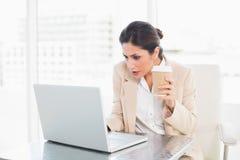 Concentrando il caffè bevente della donna di affari mentre lavorando al rivestimento Immagine Stock Libera da Diritti