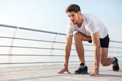 Concentrared young sportsman is ready to run outdoors Stock Photo