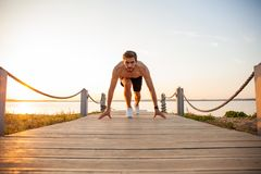 Concentrared young sportsman is ready to run outdoors in the morning. Concentrared young sportsman is ready to run outdoors in the morning royalty free stock photography