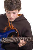 Concentrate. Teen boy concentrating seriously on his guitar chords Royalty Free Stock Images