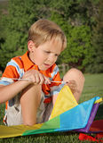 Concentrate. Close-up of young white boy concentrating on building a kite outdoors Royalty Free Stock Photography