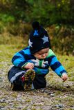 Concentrate. Boy is digging with a spoon with a very concentrated expression Stock Images