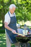 Concentrate grandfather doing barbecue. On a sunny day Royalty Free Stock Photos