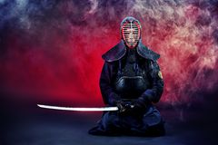 Concentrate. Handsome young man practicing kendo. Over dark background Royalty Free Stock Photo