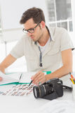 Concentrate male artist sitting at desk with photos Stock Photo