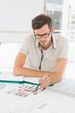 Concentrate male artist sitting at desk with photos. In the office Stock Images