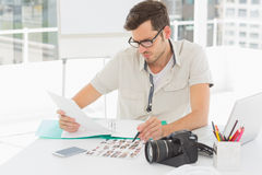 Concentrate male artist sitting at desk with photos Stock Images