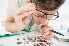 Concentrate male artist sitting at desk with photos. In the office Royalty Free Stock Images