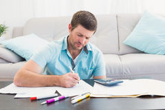 Concentrate man counting his bills. Serious man counting at home in the living room royalty free stock photos