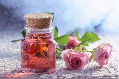 Concentrate from a rose in a glass bottle surrounded by roses and a couple, spa procedures. Stock Photography
