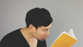 Concentrate on the yellow book. An asian man with black t-shirt Royalty Free Stock Photography