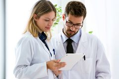 Free Concentrate Young Confident Doctors Looking Medical Reports In Digital Tablet In Medical Office. Stock Photos - 132768923