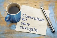 Concentrate on your strengths. Handwriting on a napkin with a cup of espresso coffee Royalty Free Stock Photography