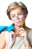 Concentrated. Mature woman holding pencil in one hand and jacket in the other looking down concentrated Stock Photo