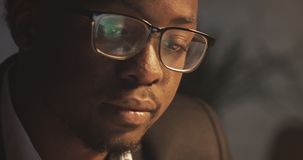 Concentrated African American businessman in eyeglasses in front of laptop with reflection of display in eyeglasses. Young male freelancer working at night stock video