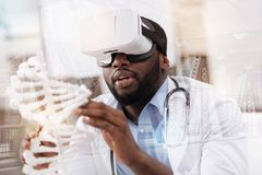Concentrated African American doctor with genome mockup. Tangible masterpiece. Close up of thoughtful African American touching genome mockup while looking at it royalty free stock photos