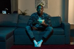 Concentrated african american man with popcorn in hands watching tv. At home stock images