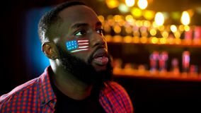 Concentrated african american man with usa flag on cheek watching news in bar royalty free stock photo
