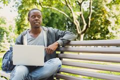 Concentrated man working on his laptop outdoors. Concentrated african-american man working on his laptop, sitting on bench in park, looking away. Technology Royalty Free Stock Images