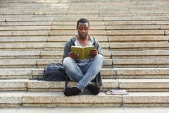 Concentrated african-american student reading book on university stairs. Preparing for exams at college or university. Education concept, copy space Royalty Free Stock Photo