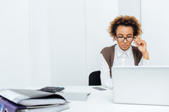 Concentrated african american woman accountant working in office using laptop. Concentrated african american young woman accountant in glasses working in office Royalty Free Stock Photo