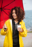 Concentrated african curly young lady walking outdoors and drinking coffee. Stock Photo