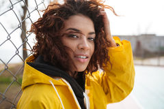 Concentrated african curly young lady wearing yellow coat. Picture of concentrated african curly young lady wearing yellow coat walking outdoors. Looking at royalty free stock image