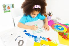 Concentrated African girl writes letters at table royalty free stock photography
