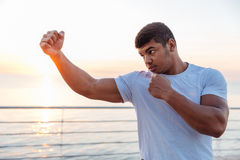 Concentrated african man boxer working out outdoors on sunrise. Concentrated african american young man boxer working out outdoors on sunrise stock photo