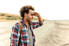 Concentrated african man standing outdoors and looking far away. Concentrated african american young man standing outdoors and looking far away Royalty Free Stock Image