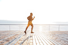 Concentrated african sportsman running on pier in the morning Stock Photo