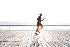 Concentrated african sportsman running on pier in the morning Stock Photography