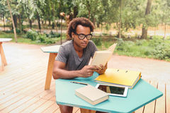 Concentrated african young man sitting and reading book. Outdoors Stock Image