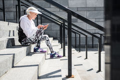 Concentrated aged lady messaging through her cellphone on stone steps Royalty Free Stock Images