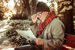 Concentrated aged man attentively reading a newspaper. Reading news. Concentrated grey-bearded aged man sitting on the park bench and reading a newspaper royalty free stock photography