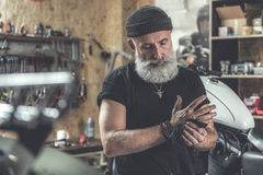 Concentrated aged man cleaning hands. Busy mature bearded biker is locating in garage. He using black rag in order to make arms clean Royalty Free Stock Photography