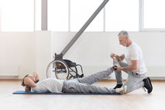 Concentrated aged orthopedist helping with disabled patient. Doing my job properly. Confident skilled aged physical therapist helping the disabled men and Stock Photography