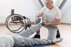 Concentrated aged orthopedist helping the disabled patient in the gym. Full of concern. Involved skilled powerful physical therapist helping the invalid and Royalty Free Stock Photography
