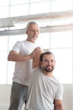 Concentrated aged orthopedist helping a handicapped in the gym. Enjoying helping people. Involved positive confident orthopedist helping the disabled men doing Stock Images